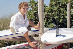 Young boy sitting on surfboards Royalty Free Stock Photo