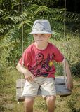 Young boy sitting on swing wearing hat royalty free stock photo