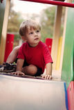 Young Boy Sitting at Top of Slide Stock Photography