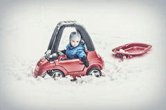 Young Boy Sitting in a Toy Car Pulling a Sled Stock Photography
