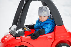 Young Boy Sitting in a Toy Car Stuck in the Snow - Close Up. A young boy dressed for cold weather with a serious expression sits in a red toy car stuck in the Royalty Free Stock Photo