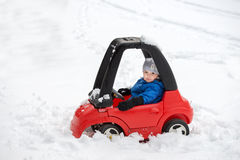 Young Boy Sitting in a Toy Car Stuck in the Snow. A young boy dressed for cold weather sits in a red toy car stuck in the snow during the winter season stock photography