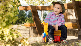 Young boy sitting in a toy dump truck Stock Photos