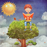 Young boy sitting on a tree and reads a book Stock Images
