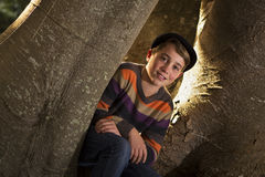Young boy sitting beside tree trunk Royalty Free Stock Images