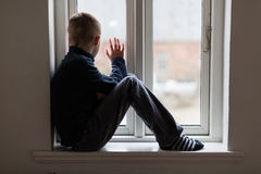 Young boy sitting on a windowsill waving. Young boy sitting on a windowsill inside a house waving to someone outside, view from the side Royalty Free Stock Images