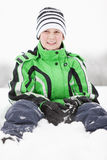 Young boy sitting in winter snow Royalty Free Stock Photo