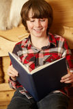Young Boy Sitting On Wooden Seat Reading Book Royalty Free Stock Image