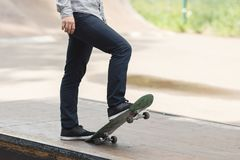 Young boy skater in the park. Unidentified stylish young male skateboarder preparing to ride sketchboard by lifting it with one foot in the park on warm summer Stock Photography