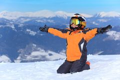 Young Boy Skier. Sitting in snow with arms stretched out Stock Image