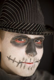 Young boy in skull makeup for Halloween. Wearing a dark striped hat and dark cloak, close up of his face in a horror genre stock image