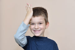 Young boy slapping hand on head Royalty Free Stock Photography
