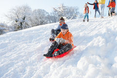 Young Boy Sledging Down Hill With Family Watching Stock Photos