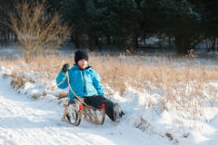 Young boy sledging downhill Stock Photography
