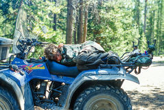 Young Boy Sleeping on a ATV Four Wheeler. Landscape composition of a young boy sleeping curled up on the seat of an ATV four wheeler. ATV is parked in a camping Stock Images