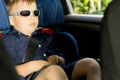 Young boy sleeping in the child car-seat Stock Images
