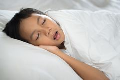 Young boy sleeping with mouth open snoring. On bed white pillow and sheet.boy asleep and snoring.sleep concept stock images