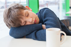 Young boy is sleeping on table with empty cup Royalty Free Stock Images