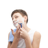 Young boy in a sleeveless shirt. Young boy in a sleeveless white shirt with his face covered with the shaving foam, in process of shaving, composition isolated Royalty Free Stock Photos