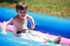 Young boy sliding Stock Photos