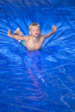 Young boy sliding down a slip and slide outdoors Royalty Free Stock Image