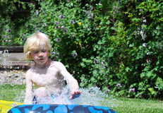Keep Kids Cool with Water Games this Summer. Young blond boy sliding on a plastic water slide which is on grass and surrounded by flowering scrubs on a hot Royalty Free Stock Images