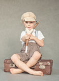 Young boy with a slingshot. A five year old boy sitting on an old suitcase and aiming with a slingshot Royalty Free Stock Photo