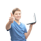 Young boy with a small notebook computer. Young boy in a blue t-shirt with a small notebook computer in his hands in front of him while showing thumbs up Royalty Free Stock Photo