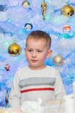 Young boy and smas tree Stock Photo