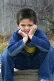 Young Boy Smiles. Portrait of a young boy sitting down with with hands on his face and a nice smile Royalty Free Stock Images