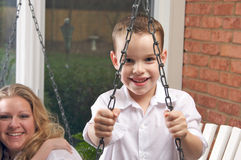 Young Boy Smiles for The Camera. As His Mom Looks On Stock Photography