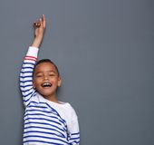 Young boy smiling with arm raised Stock Photos