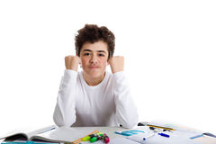 Young boy smiling on homework makes success gesture Stock Photos