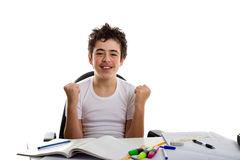 Young boy smiling on homework makes success gesture Stock Image