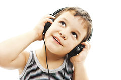 The young boy is smiling and listening to music, looking up Stock Photography