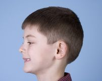 Young Boy Smiling Side Profile. Young boy head shot smiling side profile with blue background stock images