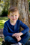 Young Boy smiling and sitting crossed legged against tree trunk Stock Image