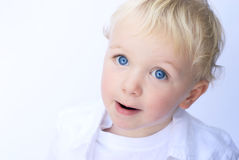 Young boy smiling on white background. Happy young boy with subtle smile on white background Royalty Free Stock Photo