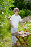 Young boy snacking fresh picked strawberries in  a. Little blonde boy snacking strawberries in a flowering garden in spring Royalty Free Stock Photos