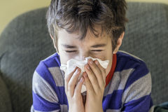 Young boy sneezing into a tissue while at home sick in pyjamas Royalty Free Stock Image