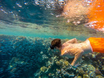 Young boy Snorkel swim in shallow water with coral school of fis. Young boy snorkel swim in underwater exotic tropics paradise with school of fish on coral reef Stock Photo