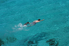 Young boy snorkeling in crystal clear water Stock Photo