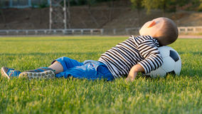 Young boy with a soccer ball. Young boy lying on the grass in a park resting his head on a football or soccer ball Stock Photography