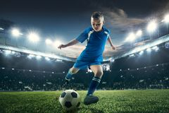 Young boy with soccer ball doing flying kick at stadium stock photography