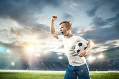 Young boy with soccer ball doing flying kick at stadium. Young boy with soccer ball at stadium. football soccer player on sky background as winner royalty free stock photo