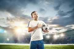 Young boy with soccer ball doing flying kick at stadium. Young boy with soccer ball at stadium. football soccer player on sky background as winner stock photos