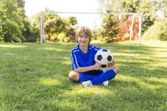 Young boy with soccer ball on a sport uniform Stock Images