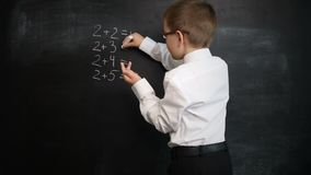 Young boy solving maths expression on a blackboard. Creative concept of back to school and study. Pre school stock video footage