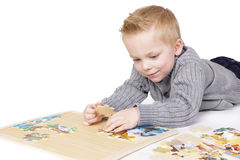 Young boy solving a puzzle. A cute young boy solving a jigsaw puzzle. Isolated on white background stock image