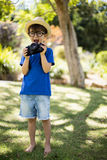 Young boy in spectacles holding a camera. Happy young boy in spectacles holding a camera in park Stock Image